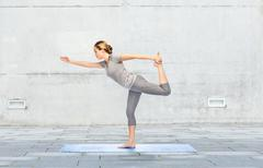 woman making yoga in lord of the dance pose on mat - stock photo