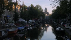 Canal in Amsterdam with the Basillica St Nicholas Stock Footage