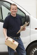 Courier Delivering Package Standing Next To Van - stock photo