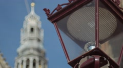 Pull focus from Old Amsterdam streetlamp to the De Oude Kerk - stock footage