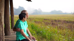 Asian senior couple sitting next to rice field. Farm and agricultural business Stock Footage