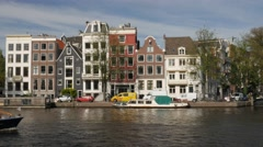 Amsterdam tour boat sails along the wide Amstel Canal in Amsterdam Stock Footage