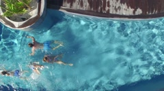 Upper view of family swimming in private swimming-pool Stock Footage