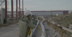Girl with Land Surveyor Total Station on the Background of Construction Stock Footage