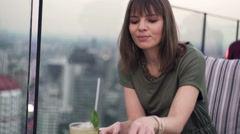 Young woman relaxing and drinking mojito in bar Stock Footage