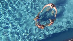 Aerial view of family in swimming pool making circle together - stock footage