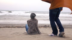 Man give scarf to his girlfriend on windy day by the sea, slow motion Stock Footage