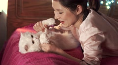 Girl playing in bed with her cat Stock Footage