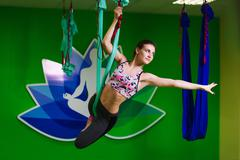 Aerial yoga practicing - anti gravity yoga with scarves - stock photo