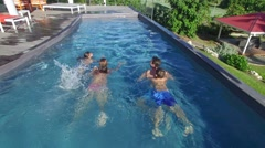 Family swimming in private swimming-pool Stock Footage