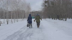 Two Women Hastily Walk on the Snow-Covered Road Bare Trees on the Both Sides of Stock Footage