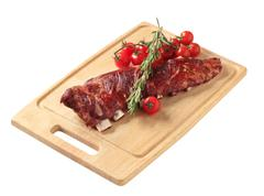 Smoked pork spare ribs on a cutting board - stock photo