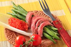 Strips of roast beef with green beans Stock Photos