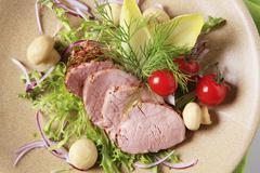 Roast pork tenderloin served with vegetables and mushrooms - stock photo