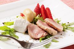 Slices of roasted pork tenderloin and accompaniment Stock Photos