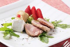 Slices of roasted pork tenderloin and accompaniment - stock photo
