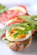 Brown bread roll with roasted bacon and egg - stock photo