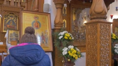Old Golden Looking Icons in Orthodox Cathedral, and People Walking and Praying Stock Footage