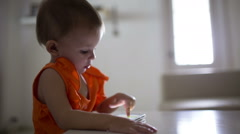 A young child plays on a modern smartphone in the interior Stock Footage
