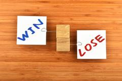 Win lose, two paper notes in different directions on wood - stock photo