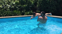 Boy / kid and father or adult having fun / playing in swimming pool. Slow Motion - stock footage