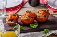 Baked tomatoes stuffed with herbs - stock photo
