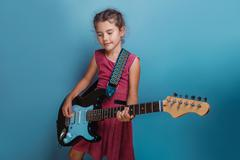 Girl  European  appearance ten years  playing guitar on a blue - stock photo