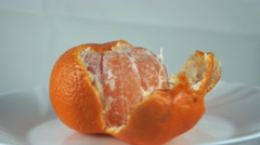 Peeled tangerine on a plate moves. Stock Footage