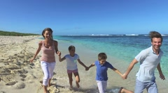 Family of four running on a caribbean beach - stock footage