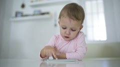 A young child plays on a modern smartphone in the interior - stock footage