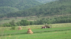 4K Agriculture View, Farmers in Mountains Field Loading Hay in Cart, Tractor Stock Footage