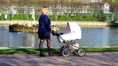 Woman walking in the park with pink stroller Stock Footage