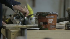 Man painting timber stain onto a piece of wood Stock Footage