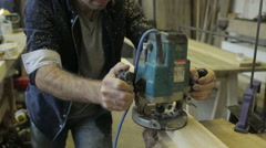 Man using a router on a piece of wood in a workshop Stock Footage