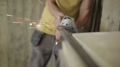 Man in workshop using an angle grinder on a length of steel tube in a vice - stock footage