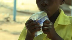 CLOSE UP: PAKRO BOY STUDENT DRINKS SACHET WATER Stock Footage