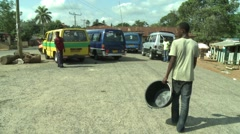 PAKRO YOUNG MAN CARRIES EMPTY WATER CONTAINER PAST VANS- CAMERA FOLLOWS - stock footage