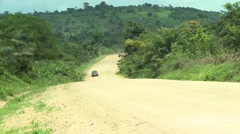 PAKRO: CAR DRIVES UP DIRT ROAD PAST CAMERA Stock Footage