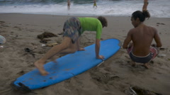 Learning how to get up on a surf board during a beginning surf lesson Stock Footage