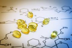 Chemistry science formula and oil capsules. Medicine concept - stock photo