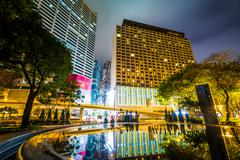 Skyscrapers and a fountain at Victoria Park at night, in Causeway Bay, Hong K Stock Photos