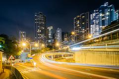 Long exposure of traffic on Upper Albert Road, and modern skyscrapers at nigh Stock Photos
