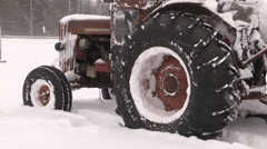 Old antique farm tractor still running today as snow plow in winter storm Stock Footage