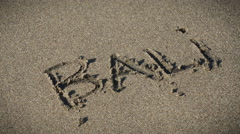 A wave washes away the word Bali written in the sand Stock Footage