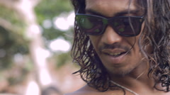 A young Balinese man with wavy hair looks at the camera and smiles Stock Footage