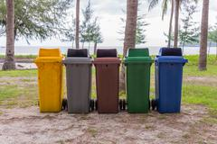 trash cans in the park beside the walk way - stock photo
