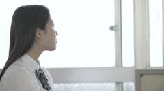 Japanese high-school student looking out of the window - stock footage