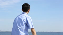 Young Japanese man sitting on stone fence by the sea Stock Footage