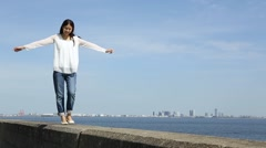 Young Japanese woman walking on stone fence by the sea Stock Footage