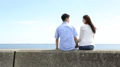 Young Japanese couple sitting on stone fence by the sea Stock Footage